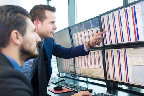 two men looking at bank of computer screens. day traders